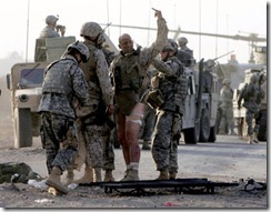 mnw15bombs1<br /> MUST CREDIT: Jeff Bundy/The Omaha World-Herald<br />            Gunnery Sgt. Michael Burghardt signals his defiance after being struck by an IED Monday Sept. 19, 2005 near Ramadi, Iraq.  The Marine refused to be carried away on a streacher and walked under his own power to a waiting medavac.  Attending to the marine was Nebraska 167 CAV members Spc. John Adams (far left in front)  and PFC. Darin Nelson of Fremont Neb.  Burghardt is an EOD with the United States Marine Corps.  (Staff photo by Jeff Bundy/the Omaha World-Herald)<br /> (mnw# 42p cm)